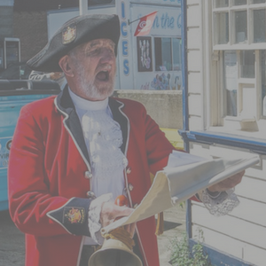 A Town Crier wearing a red coat making an important announcement